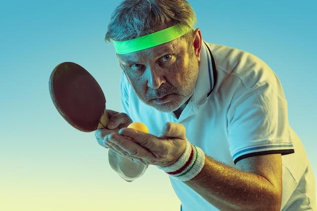 ネオンの光のグラデーションの背景で卓球をしている年配の男性。素晴らしい形の白人男性モデルは、アクティブでスポーティーなままです。