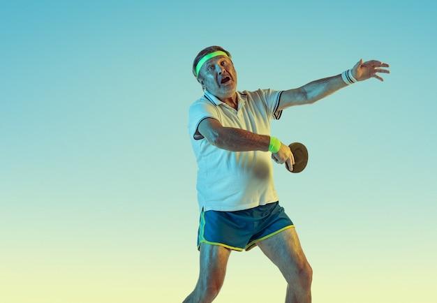 Старший мужчина играет в настольный теннис на стене градиента в неоновом свете. кавказский мужчина-модель в отличной форме остается активным, спортивным. понятие спорта, активности, движения, благополучия, здорового образа жизни.