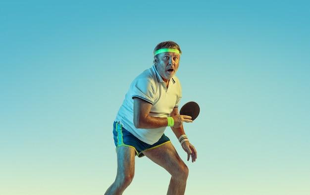 Старший мужчина играет в настольный теннис на градиентной стене в неоновом свете