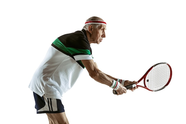 Senior man playing tennis in sportwear isolated on white wall