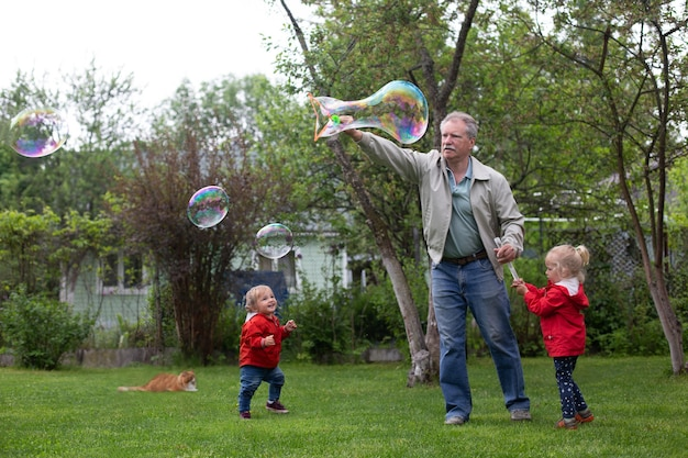 Senior man playing with his grandchildren in garden