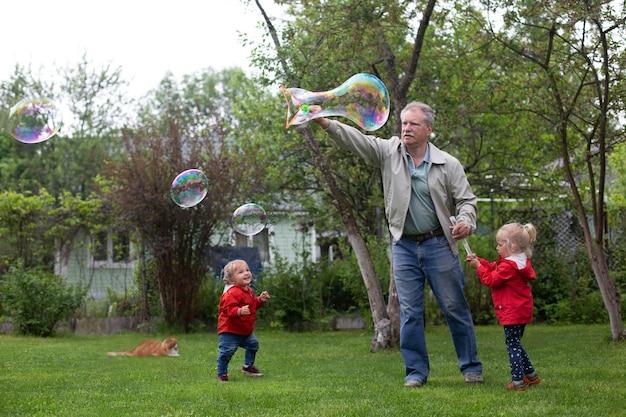 庭で孫と遊ぶ年配の男性