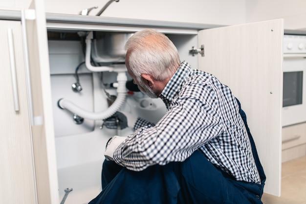 Старший мужчина-сантехник, работающий с сантехническими инструментами на кухне. ремонт.