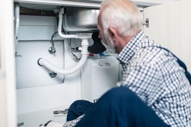 Старший мужчина-сантехник, работающий с сантехническими инструментами на кухне. ремонт. Premium Фотографии