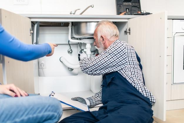 キッチンで配管ツールを使用して作業している年配の男性配管工。リノベーション。