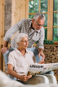 Senior man pointing at newspaper hold by her wife