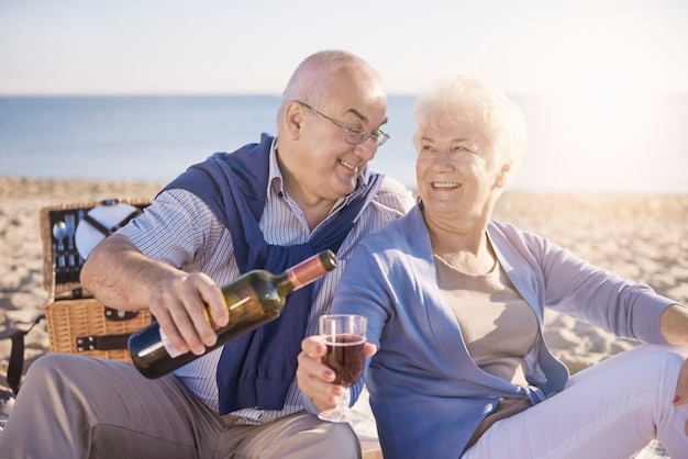 해변, 은퇴 및 여름 휴가 개념에 레드 와인을 붓는 수석 남자