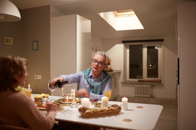 部屋のテーブルで妻と夕食をとりながらグラスに赤ワインを注ぐ年配の男性