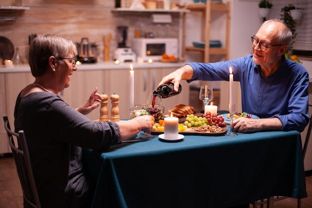 キッチンで結婚記念日を祝いながら妻にワインを注ぐ年配の男性。ダイニングルームのテーブルに座って、話し、食事を楽しんでいるロマンチックなカップル。