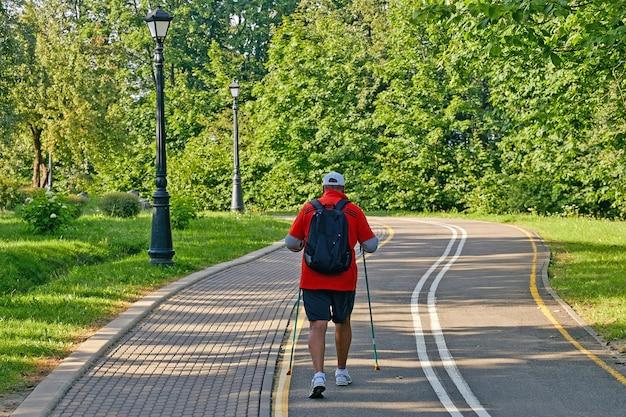 Старший мужчина, практикующий скандинавскую ходьбу, вид сзади