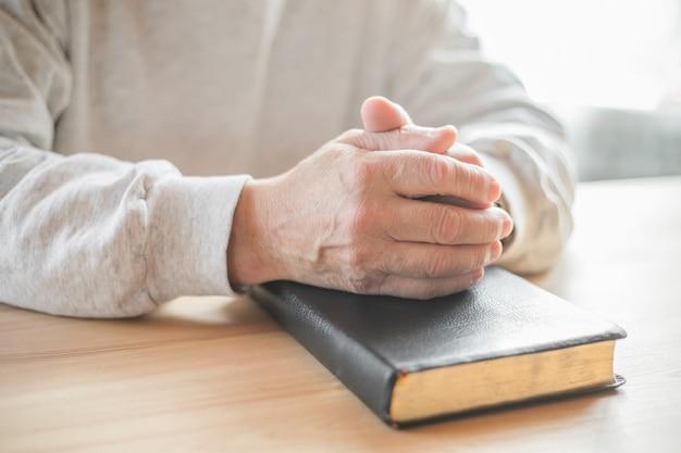 Senior man praying, reading  an old bible in his hands.