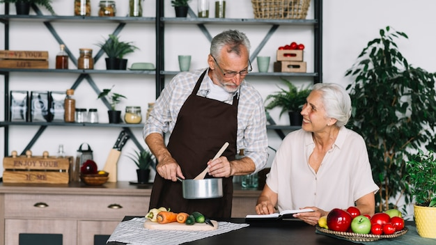 Senior man preparing food looking at book hold by senior woman
