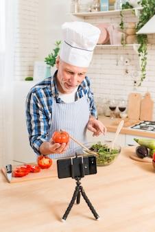 Старший мужчина готовит салат, делая видео звонок на мобильном телефоне, показывая помидоры семейной реликвии в руке