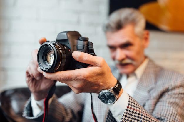 年配の男性、プロの写真家は、現代のカフェテリアで時間を過ごしている間、古いフォトカメラを持っています。