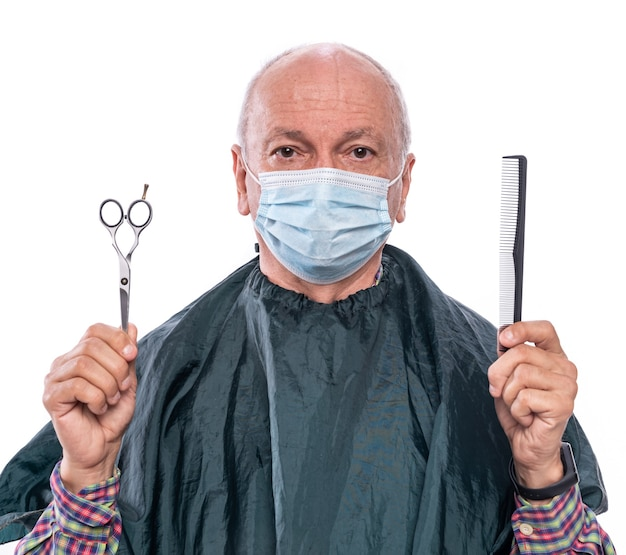 Senior man in protective face mask  holding scissors and comb