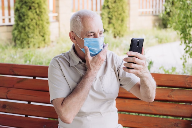 Senior man in protective face mask respirator touching his face, outbreak of viral disease coronavirus covid-2019