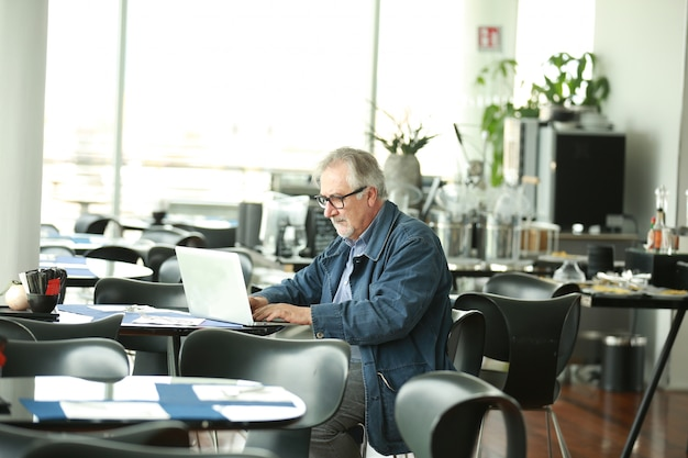 Senior man at public place connected on laptop computer