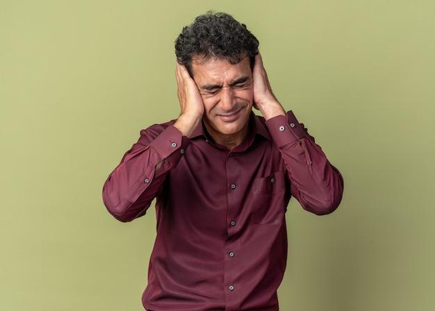 Uomo anziano in camicia viola che copre gli occhi con le mani con espressione infastidita che si posa su sfondo verde