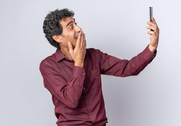 Uomo anziano in camicia viola che fa selfie usando lo smartphone che sembra sorpreso e stupito in piedi sul bianco