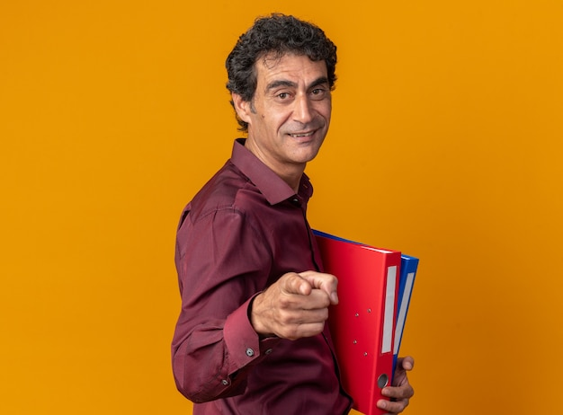 Senior uomo in camicia viola hlding cartelle guardando la fotocamera che punta con il dito indice alla fotocamera sorridente con faccia felice in piedi su sfondo arancione