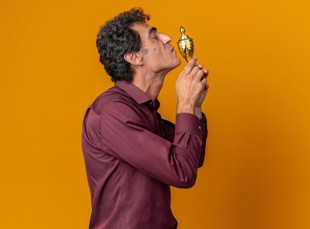 Uomo anziano in camicia viola che tiene un trofeo che lo bacia felice e allegro in piedi su uno sfondo arancione