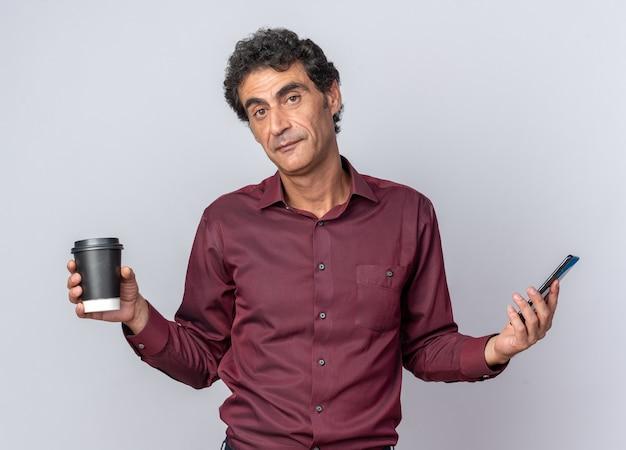Uomo anziano in camicia viola che tiene in mano un bicchiere di carta e uno smartphone che guarda la telecamera con un sorriso sul viso in piedi sopra il bianco