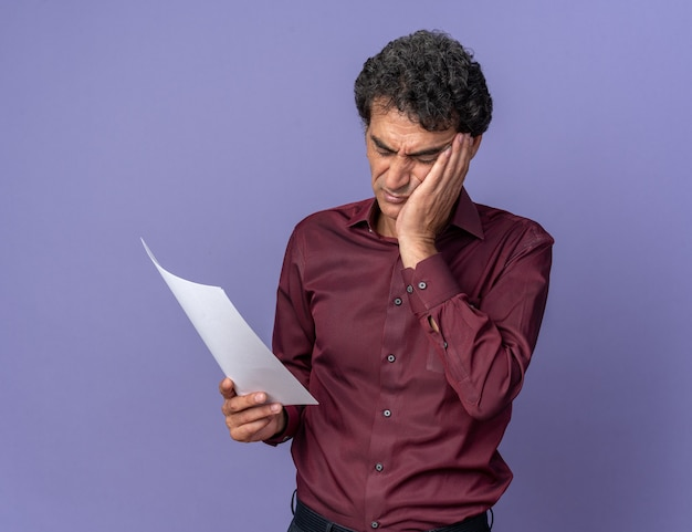 Uomo anziano in camicia viola che tiene in mano una pagina bianca che la guarda con un'espressione confusa in piedi sopra il blu