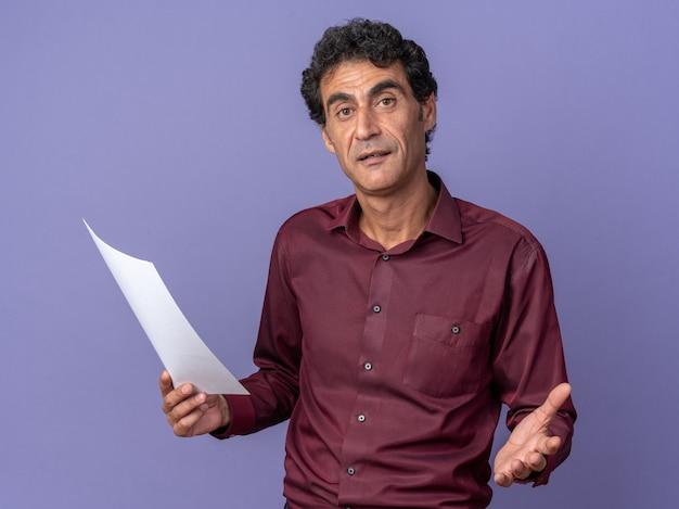 Uomo anziano in camicia viola con pagine bianche che guarda la telecamera confusa in piedi sopra il blu
