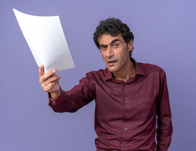Uomo anziano in camicia viola con pagine bianche che guardano la telecamera con una faccia arrabbiata in piedi sopra il blu