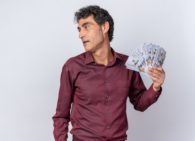 Senior man in purple shirt holding cash looking aside happy and confident standing over white