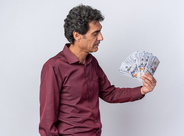 Senior man in purple shirt holding cash looking at money with serious face