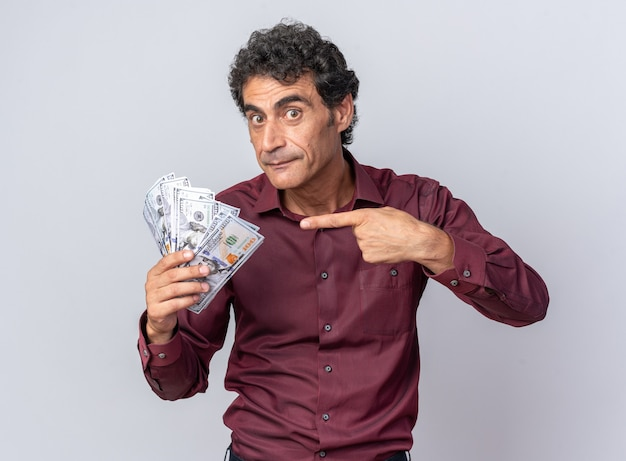 Senior man in purple shirt holding cash pointing with index finger at money looking surprised and happy