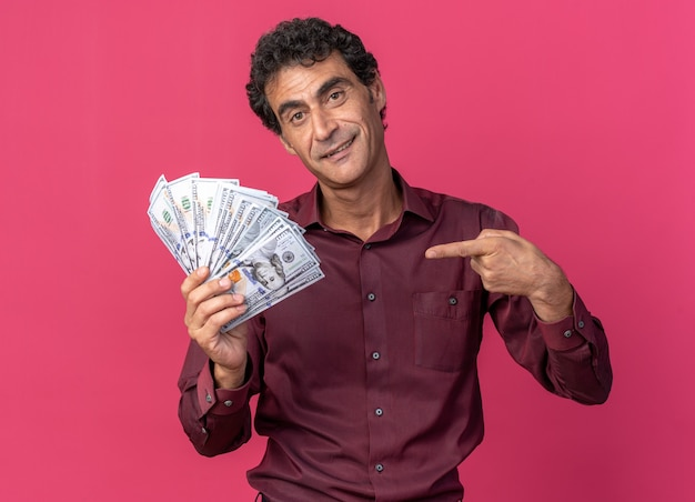 Senior man in purple shirt holding cash pointing with index finger at money smiling cheerfully looking at camera standing over pink