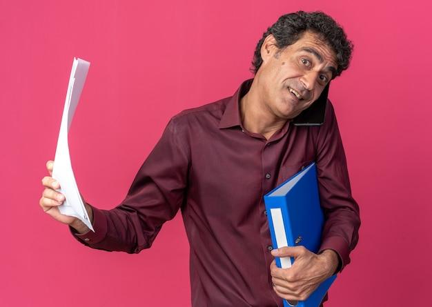 Uomo anziano in camicia viola che tiene cartella e pagine bianche guardando la telecamera confusa sorridente