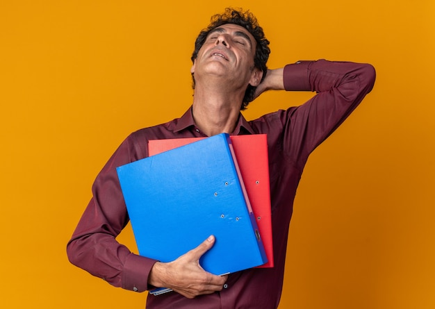 Senior man in purple shirt holding folders loking tired and overworked standing over orange background