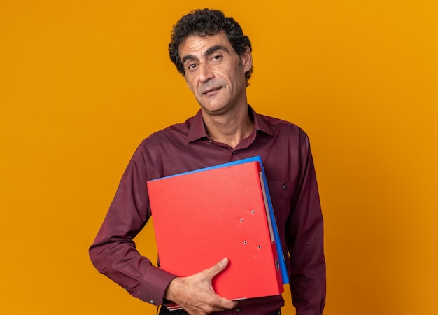 Senior man in purple shirt holding folders looking at camera with serious confident expression standing over orange background