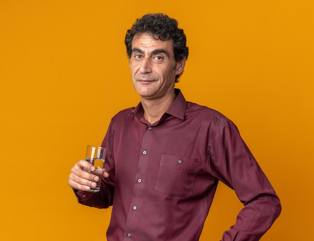 Senior man in purple shirt holding glass of water looking at camera smiling confident standing over orange background