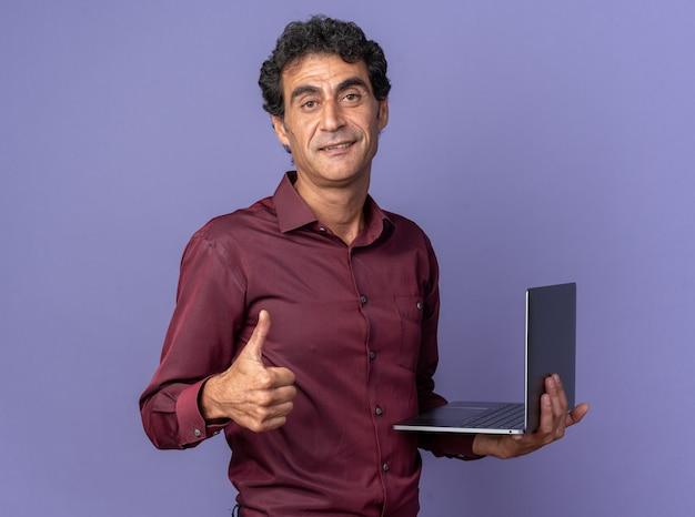 Uomo anziano in camicia viola che tiene in mano un computer portatile che guarda la telecamera sorridendo fiducioso che mostra i pollici in su in piedi su sfondo blu