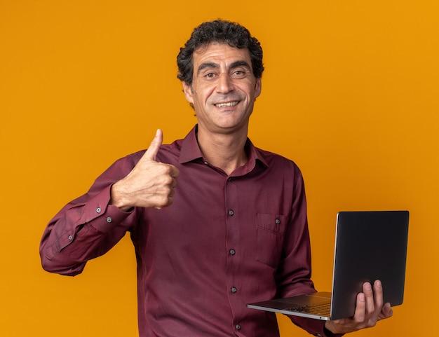 Uomo anziano in camicia viola che tiene in mano un computer portatile che guarda la telecamera sorridendo fiducioso che mostra i pollici in su in piedi su sfondo arancione