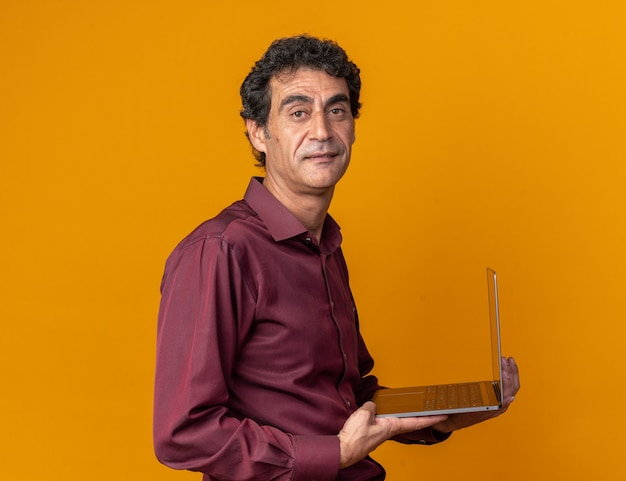 Senior man in purple shirt holding laptop looking at camera smiling confident standing over orange