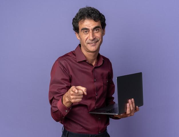 Uomo anziano in camicia viola che tiene in mano un laptop che punta con il dito indice alla telecamera sorridendo fiducioso in piedi sopra il blu