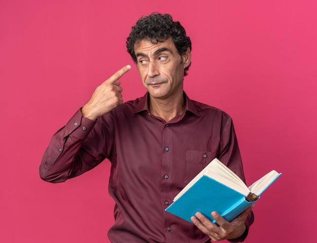 Uomo anziano in camicia viola che tiene un libro aperto che punta con il dito indice alla tempia che sembra fiducioso in piedi sopra il rosa