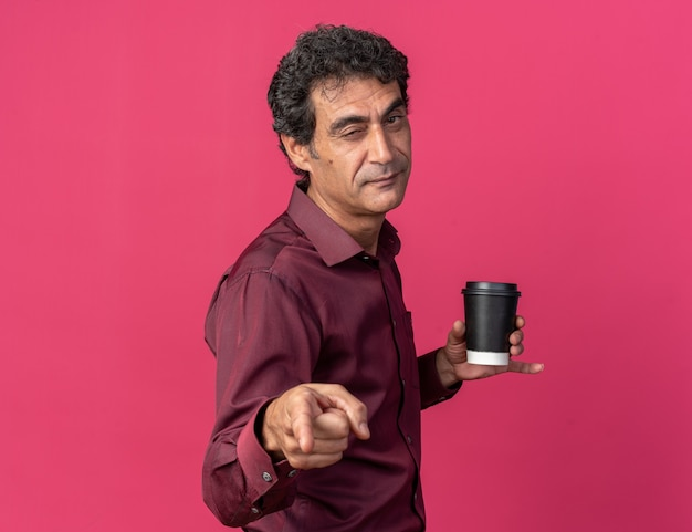 Uomo anziano in camicia viola che tiene in mano un bicchiere di carta che punta con il dito indice alla telecamera sorridendo e strizzando l'occhio