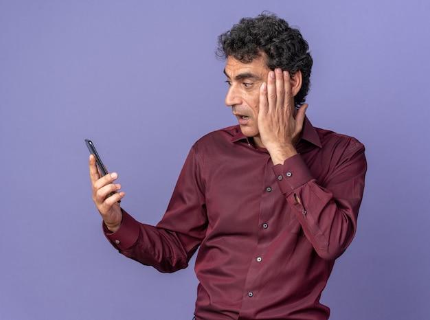 Uomo anziano in camicia viola che tiene in mano uno smartphone guardandolo stupito e sorpreso in piedi su sfondo blu