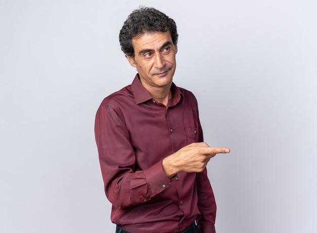 Uomo anziano in camicia viola che guarda da parte sorridente fiducioso che punta con il dito indice a lato in piedi su bianco