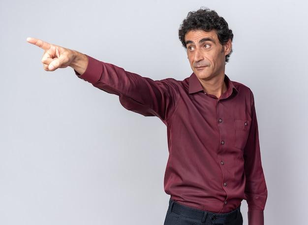 Uomo anziano in camicia viola che guarda da parte sorpreso e felice che indica con il dito indice qualcosa in piedi su sfondo bianco