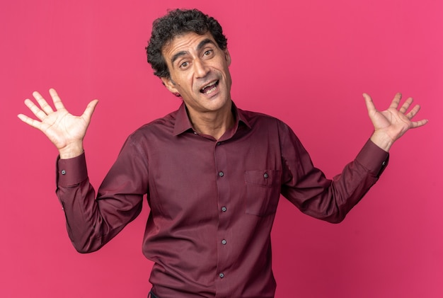 Senior man in purple shirt looking at camera confused raising arms having no answer standing over pink background