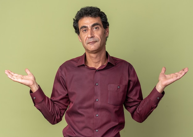 Senior man in purple shirt looking at camera confused spreading arms to the sides having no answer standing over green background