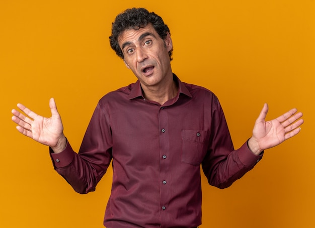 Senior man in purple shirt looking at camera confused spreading arms to the sides having no answer standing over orange background