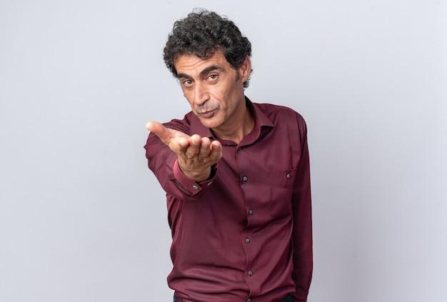 Uomo anziano in camicia viola che guarda la telecamera felice e allegro con la mano davanti a lui che soffia un bacio in piedi su sfondo bianco